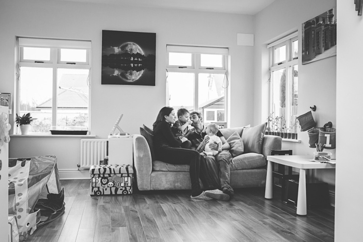 black and white image of family sitting on couch