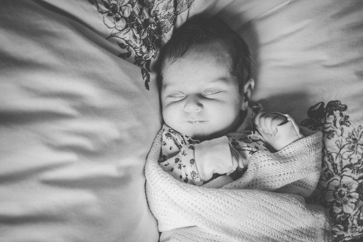 swaddled sleeping newborn on bed